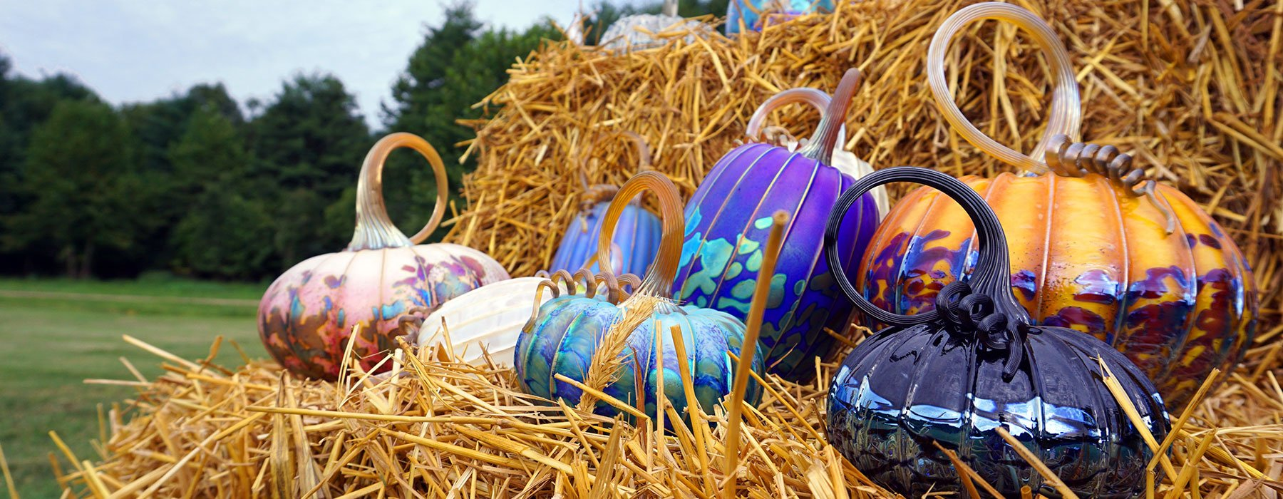 Glass pumpkins sitting on a hay bale