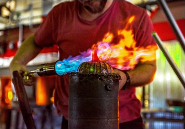 A torch being used to heat glass for the blowing process that shapes the glass