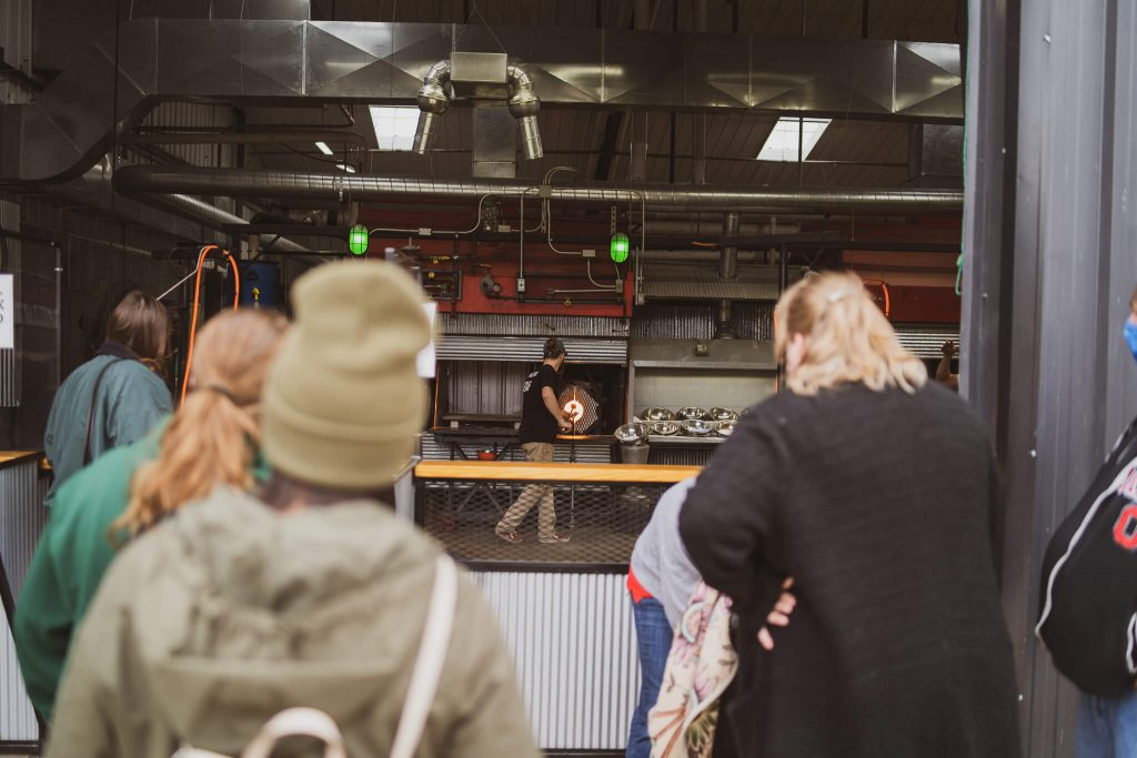 Live glass blowing demonstrations draw a crowd of onlookers