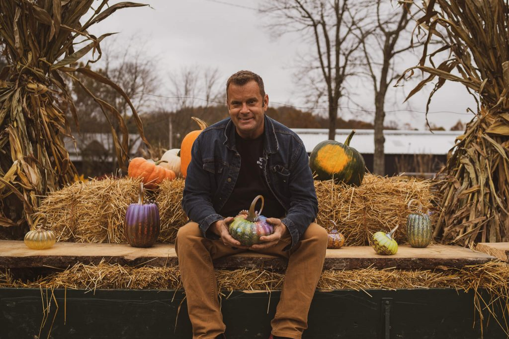 Jack Pine poses with some of his famous glass pumpkin works