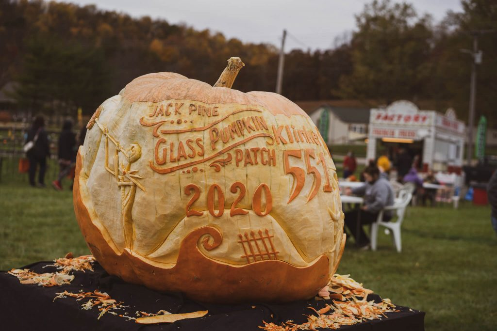 """A very large pumpkin with elaborate carving on it reads """"Jack Pine Glass Pumpkin Patch 2020"""""""